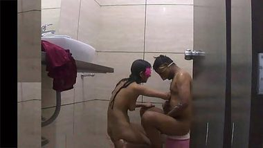 Loving Indian couple in masks helps each other during bathing